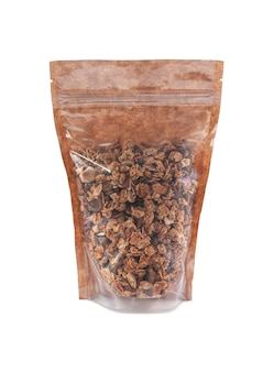Granola in a brown paper bag. doy-pack with a plastic window for bulk products. close-up. white background. isolated.