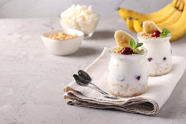 Гранола хрустящие медовые мюсли с ягодами, бананом, творогом и натуральным йогуртом, вкусный и полезный завтрак, расположенный в стеклянных банках на сером фоне, copy space