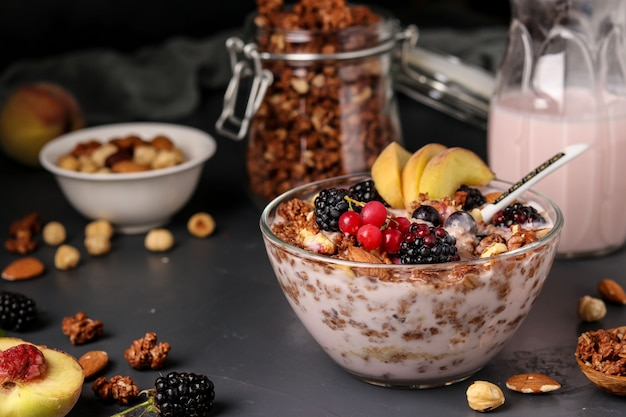 Granola crispy honey muesli with natural yogurt, fresh berries and fruit, chocolate and nuts in a glass bowl against a dark surface, healthy food