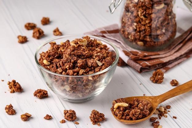 白い背景、健康食品、クローズアップ、水平方向のガラスのボウルに天然蜂蜜、チョコレート、ナッツとグラノーラクリスピーミューズリー