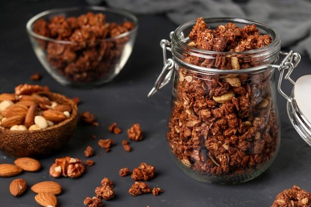 ガラスの瓶とボウルに天然蜂蜜、チョコレート、ナッツを入れたグラノーラクリスピーミューズリー