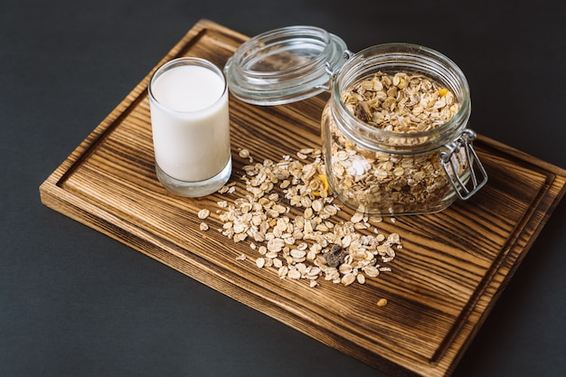 Granola in a glass jar with a glass of milk