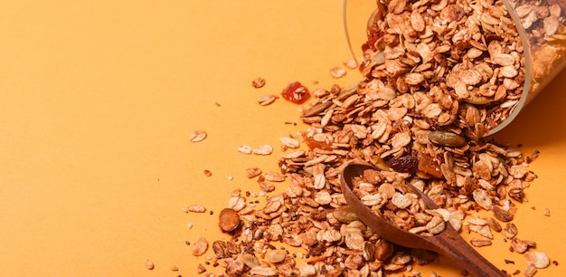Granola in a glass jar on a yellow background