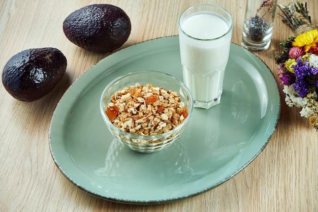 Гранола в миску с греческим йогуртом на серую тарелку на деревянном столе. вкусный, полезный и питательный завтрак. фитнес питание. крупным планом вид