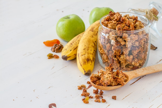 Granola and ingredients, white wood background