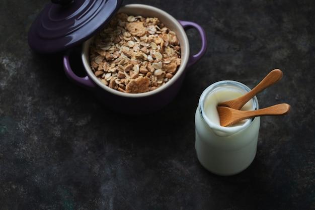 Гранола, мюсли в керамическом горшке с крышкой с йогуртом над деревенским столом. вид сверху. flat lay