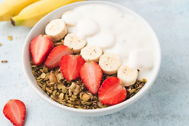 Granola, oatmeal with milk, banana and strawberry
