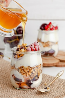 Granola parfait with red currant, cherries and pouring honey.