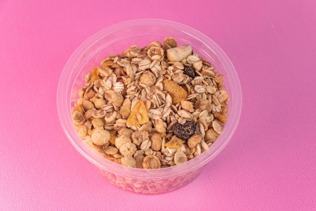 Granola in plastic bowl on the pink surface