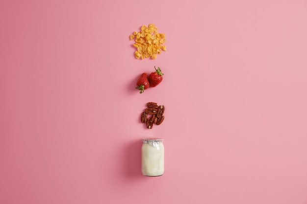 Muesli, fragole mature e noci intere come ingrediente da aggiungere per lo yogurt e per preparare gustose bevande o frullati. spuntino fatto in casa per la colazione. una sana alimentazione organica e mantenendo il concetto di dieta