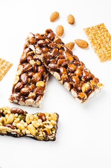 Granola; sesame seed and almonds bars on white background