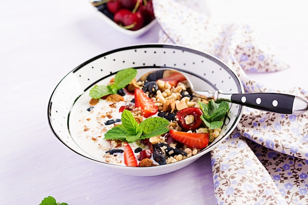 Granola, strawberries, cherry, honeysuckle berry, nuts and yogurt in a bowl