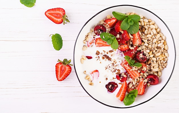 Granola, strawberries, cherry, nuts and yogurt in a bowl on a wooden table