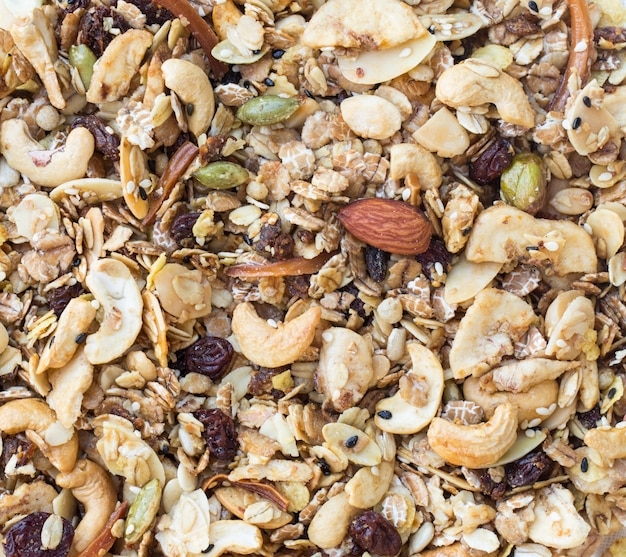 Гранола фон текстуры. куча гранолы с миндалем и семенами перед выпечкой.