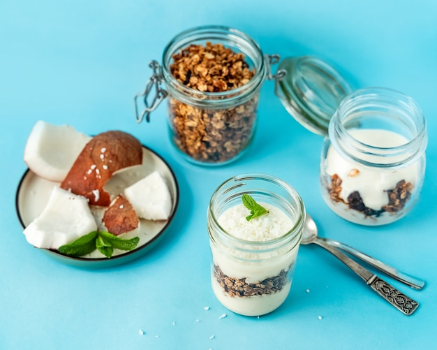 Granola and vegan coconut yougurt in glass jars on vibrant blue background