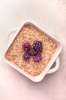 Granola in a white bowl with fresh berries on a light background in a minimalistic style