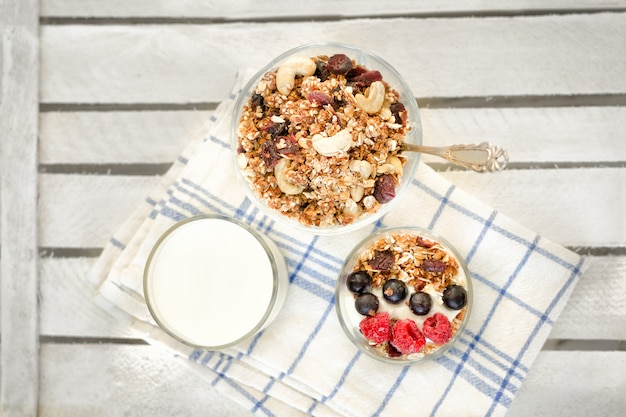 Granola with berries and nuts, a glass of yogurt on a white towel. traditional american breakfast
