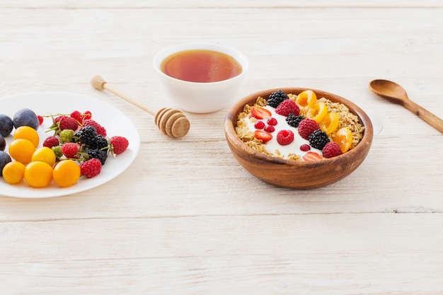 Granola with berries on white wooden wall