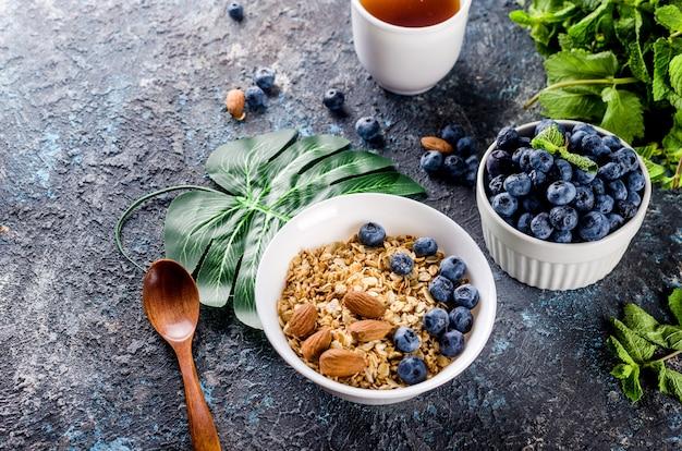 白いプレートにブルーベリーを入れたグラノーラと朝食用のお茶、ナッツと蜂蜜を添えた自家製の焼きミューズリーで甘さを抑えます。