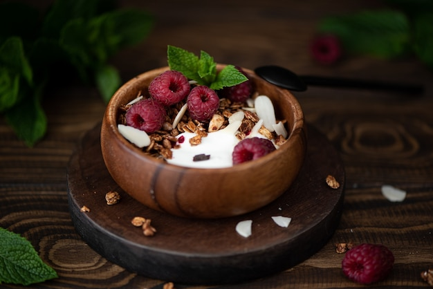 Granola with greek yogurt, mint and raspberries in wooden bowl