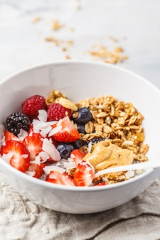 Granola with milk, chia, berries and peanut butter in a white bowl.