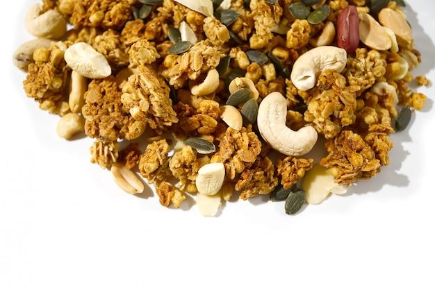 Granola при гайки изолированные на белизне. копировать пространство концепции здорового питания.