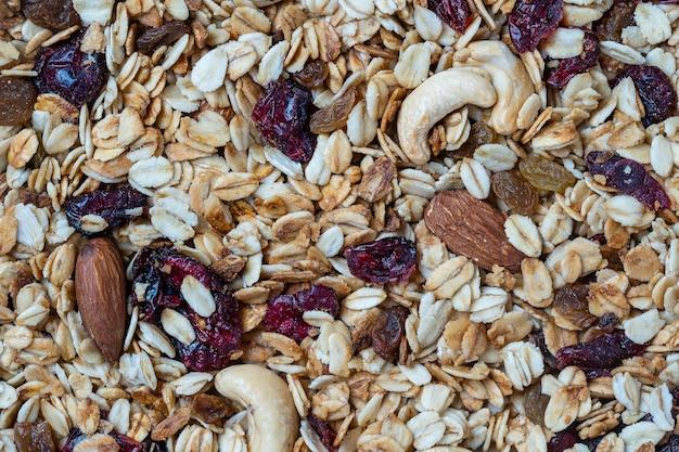 오트밀, 말린 과일, 꿀, 건포도, 마른 크랜베리, 아몬드, 캐슈 너트를 곁들인 그래놀라가 닫혀 있고, 꼭대기가 보입니다. 건강한 아침 식사 개념