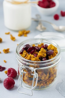 Granola with pumpkin and dried fruits for a healthy breakfast in a glass jar on a light stone or concrete table. selective focus. Premium Photo