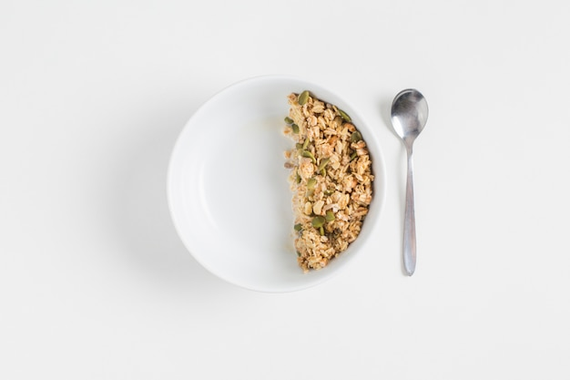 Granola with pumpkin seeds in white bowl and spoon on white background