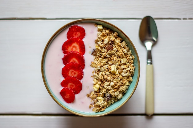 Granola with strawberries on a white wooden backdrop.