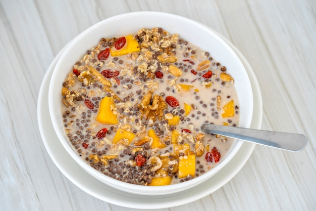 Granola with yellow mango, red goji berries and almond milk, close up, top view