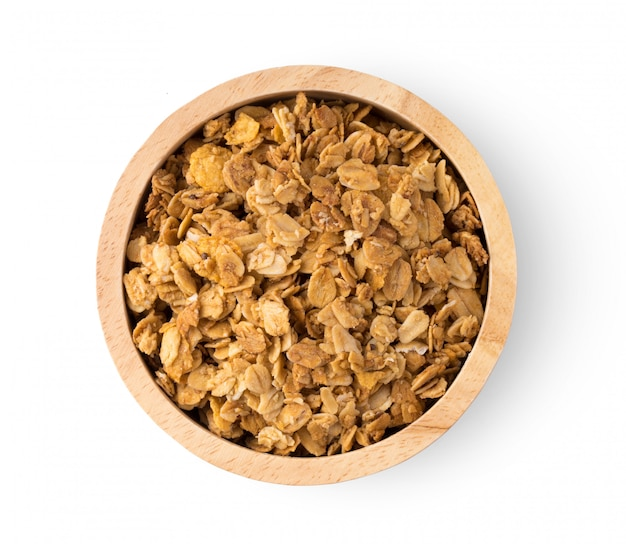 Granola in wood bowl on white wall.