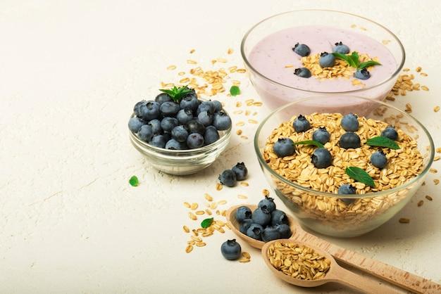 회색 배경에 있는 그릇에 그라놀라 요구르트 블루베리 건강한 아침 식사 메뉴 개념
