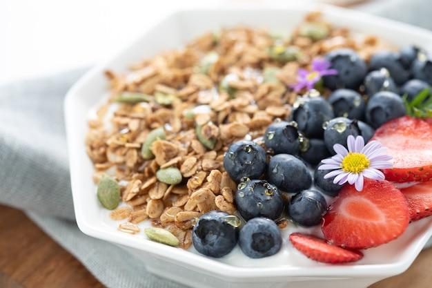 朝の健康的な食事でグラノーラヨーグルトブルーベリーピーチ朝食