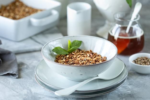 Домодельный granola в белой плите. здоровый завтрак с мюсли, йогурт, фрукты, ягоды на белом фоне в белой тарелке.