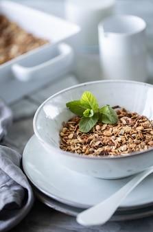 Домодельный granola в белой плите. здоровый завтрак с мюсли, йогуртом, фруктами, ягодами на белой тарелке