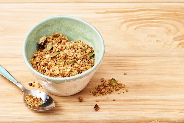 Домодельный granola в шаре на деревянном столе.