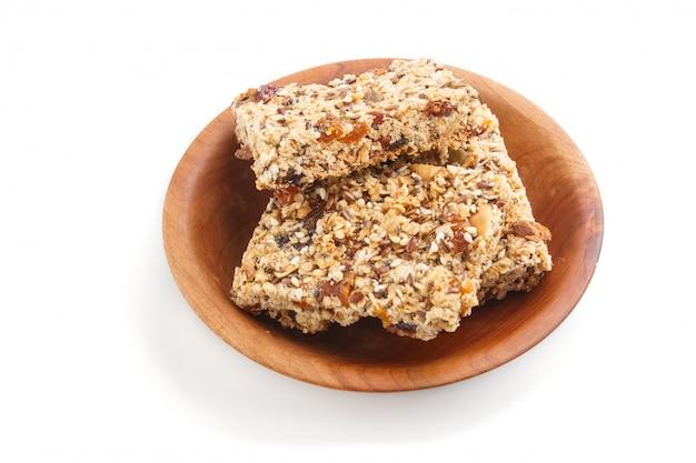 Домодельный granola от овсяных хлопьев, дат, кураги, изюма, орехов в коричневой деревянной тарелке, изолированные на белой поверхности. вид сбоку.