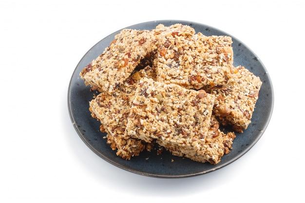 Домодельный granola от овсяных хлопьев, дат, кураги, изюма, орехов в голубой керамической пластине на белом фоне. вид сбоку.