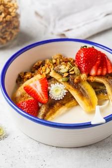 Домодельный granola с клубникой и зажаренным бананом в белом шаре.