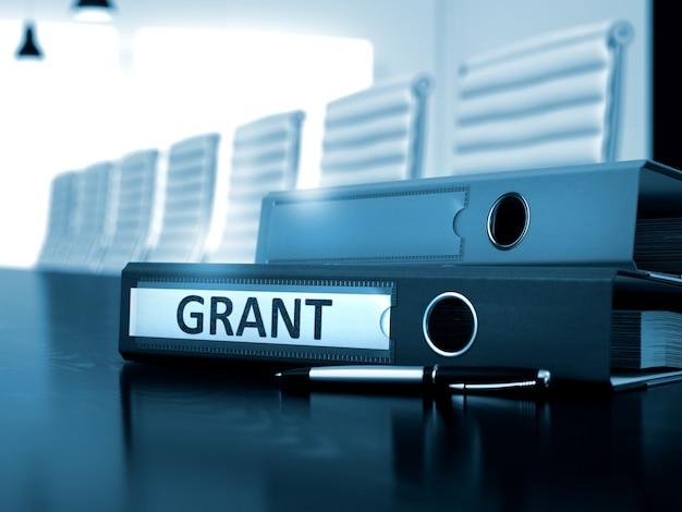 Грант - бизнес-концепция на тонированном фоне. грант. деловая иллюстрация на тонированном фоне. грант - подшивка office на рабочем столе office black. 3d.