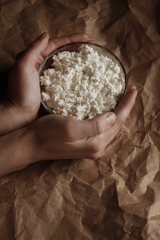 Granular curd on a brown space in the hands. milk products.