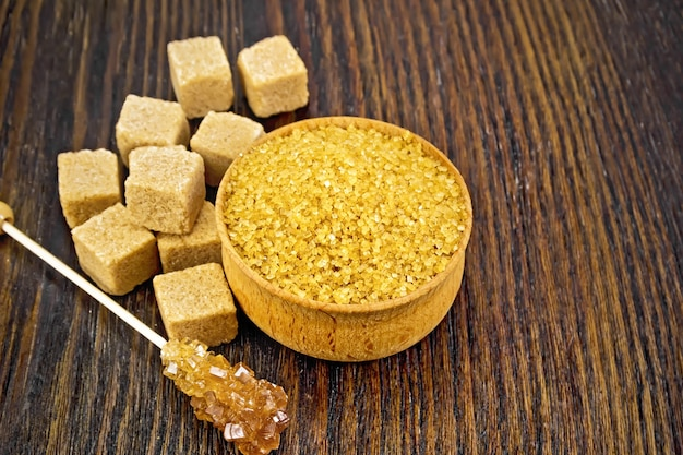 Granulated brown sugar in a bowl, crystalline on a stick and sugar cubes on wooden board background