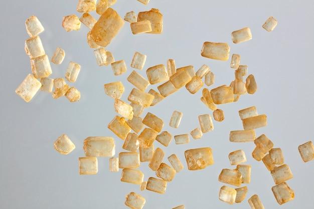 회색 배경에 공중에 떠 있는 과립된 갈색 설탕 매크로