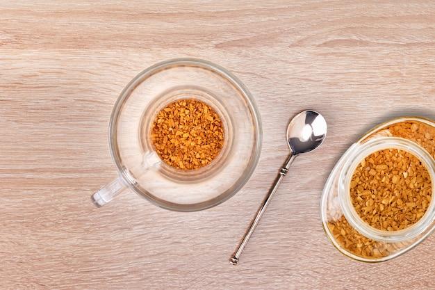 Гранулы растворимого кофе в стеклянной чашке.