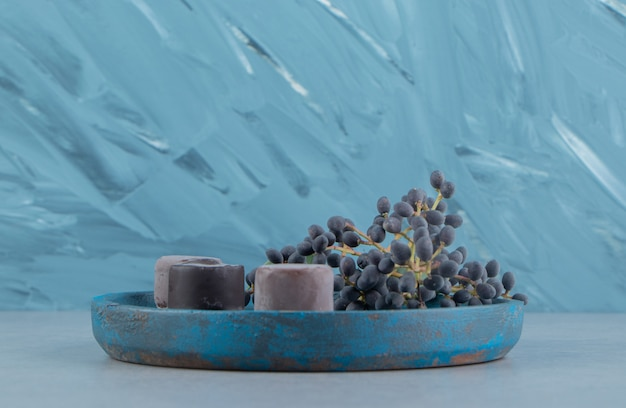 Виноград и десерт на подносе на мраморном фоне. фото высокого качества