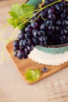 갈색 나무 배경에 파란색 그릇에 포도와 포도 나무