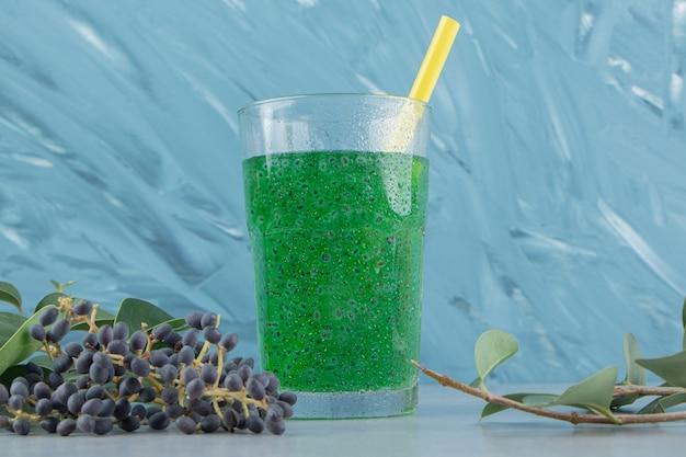 青い背景にブドウと青汁。高品質の写真
