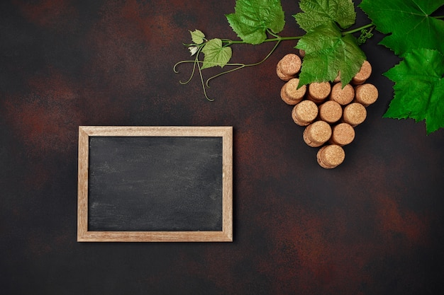 Grape bunch of cork with leaves and chalkboard on rusty background
