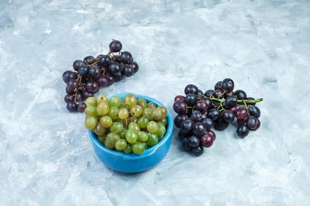 Grappoli d'uva in una ciotola vista di alto angolo su uno sfondo grigio sgangherata